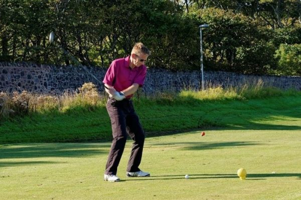 Stand in a comfortable position to hit golf ball straight